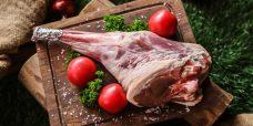 lamb leg on the wooden board prepared for cook tomato broccoli salt top view